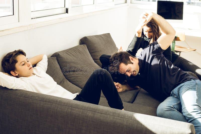 Vater, der zu Hause mit seinen Kindern auf der Couch spielt stockfotografie