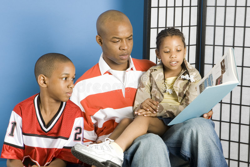 Vater, der zu seinen Kindern liest stockfotos