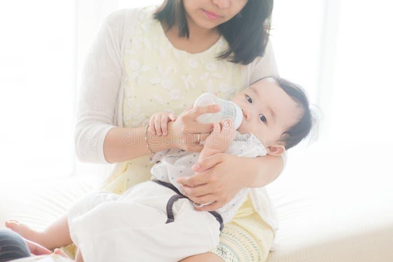Vater füttern Milch zum Baby mit der Flasche lizenzfreie stockfotografie