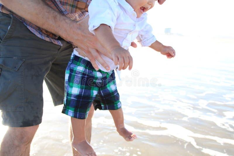 Vater hält Baby über Wellen stockfoto
