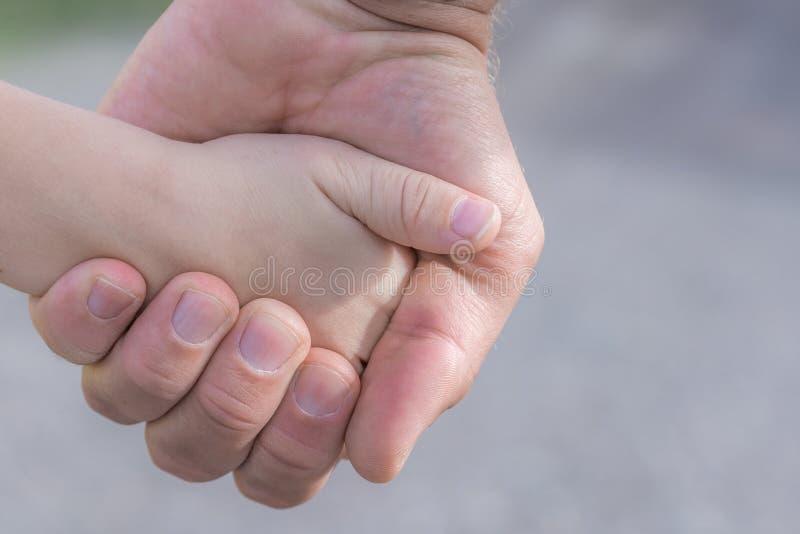 Vater hält Hand seines Kindes lizenzfreie stockfotos
