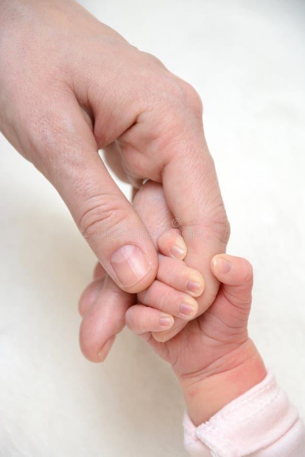 Vater Hand in Hand mit Baby lizenzfreie stockbilder