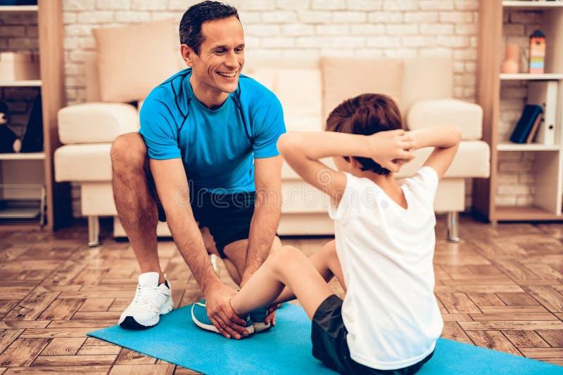 Vater-Helping Child Swing-Presse auf gymnastischer Matte stockbilder