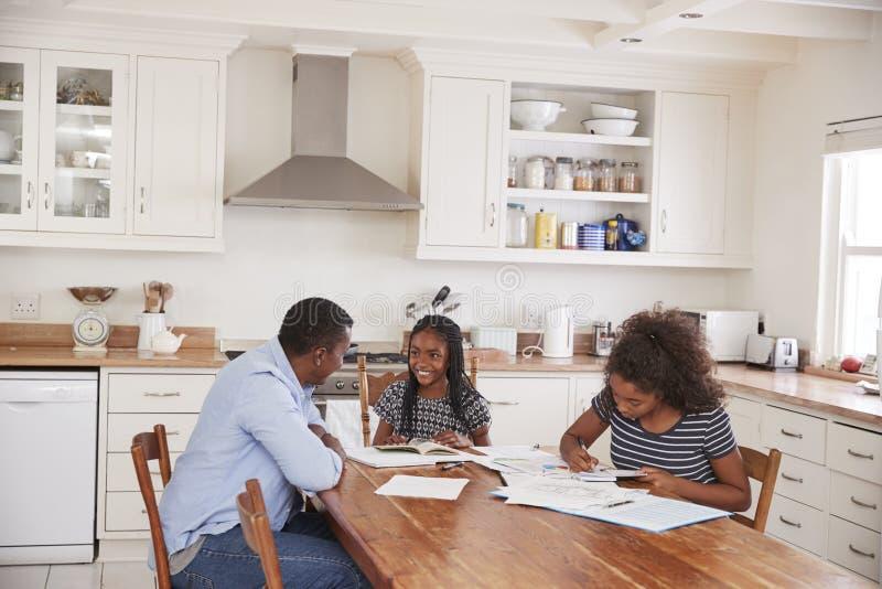 Vater Helping Two Daughters, das bei Tisch sitzt, Hausarbeit tuend stockbild