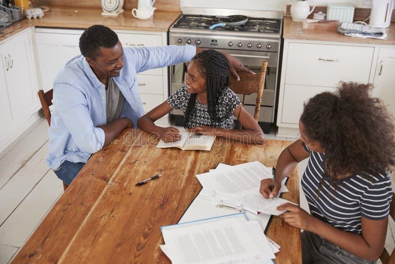 Vater Helping Two Daughters, das bei Tisch sitzt, Hausarbeit tuend lizenzfreie stockfotografie