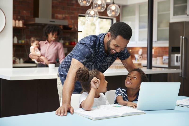 Vater-Helps Children With-Hausarbeit, während Mutter mit Baby Laptop in der Küche benutzt stockbilder