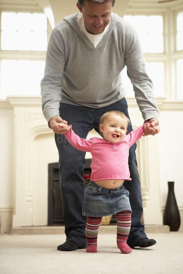 Vater hilft Schätzchen-Tochter mit dem Gehen stockfotografie