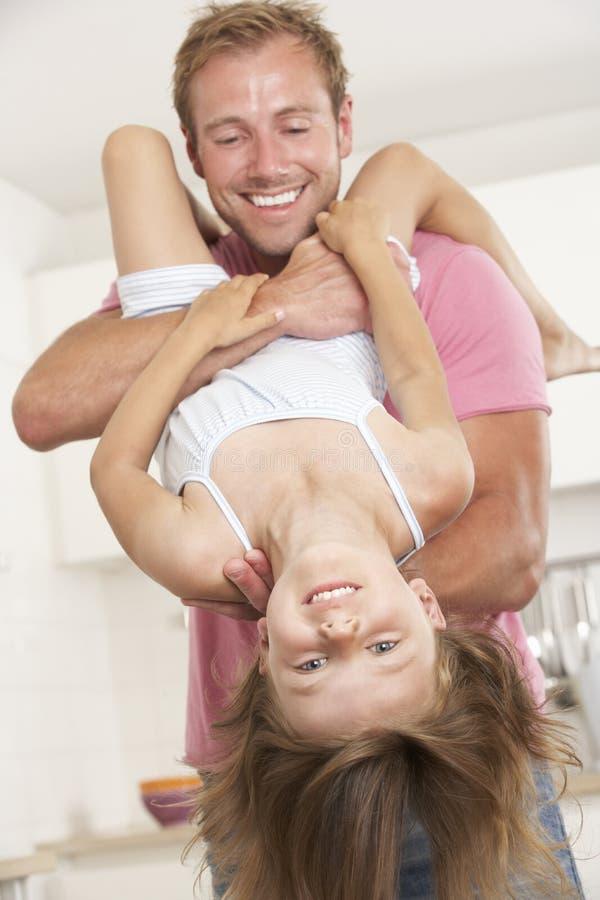 Vater Holding Daughter Upside unten zu Hause stockfotos