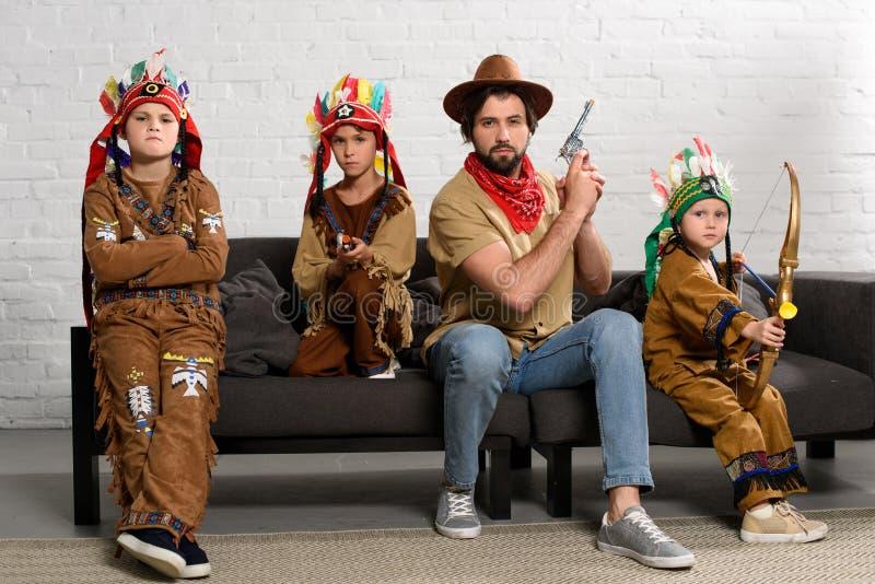 Vater im Hut und in rotem Bandana, die auf Sofa mit kleinen Söhnen in den einheimischen Kostümen sitzen lizenzfreies stockfoto