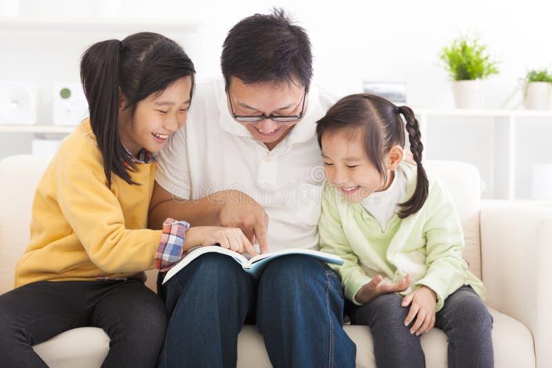 Vater las das Buch zu den Kindern stockbild