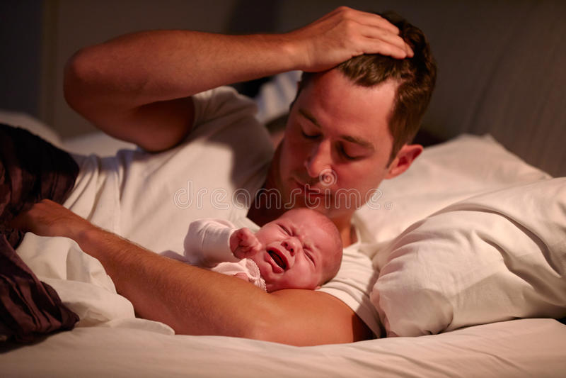 Vater Lying In Bed mit schreiender Baby-Tochter lizenzfreies stockbild