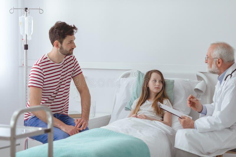 Vater mit dem Kleinkind, das über ihre Krankheit hört stockfotografie