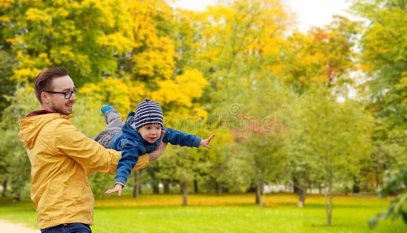 Vater mit dem Sohn, der Spaß im Herbst spielt und hat lizenzfreies stockfoto