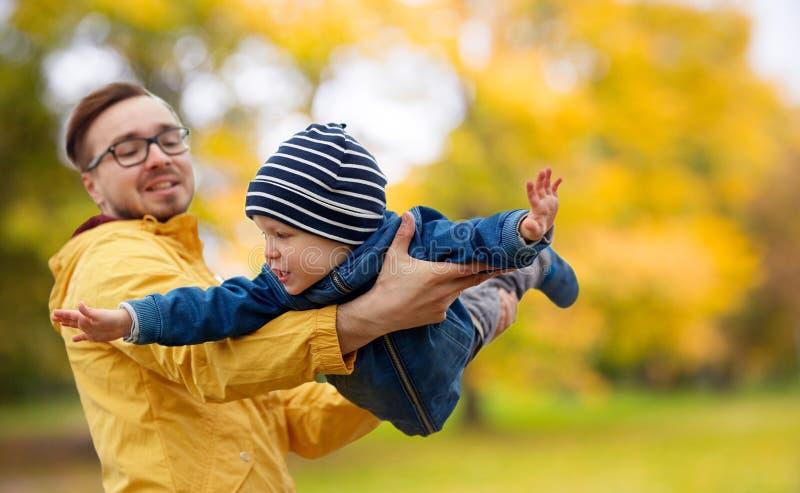 Vater mit dem Sohn, der Spaß im Herbst spielt und hat stockbilder