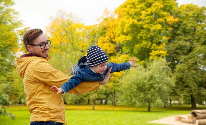 Vater mit dem Sohn, der Spaß im Herbst spielt und hat stockfotografie