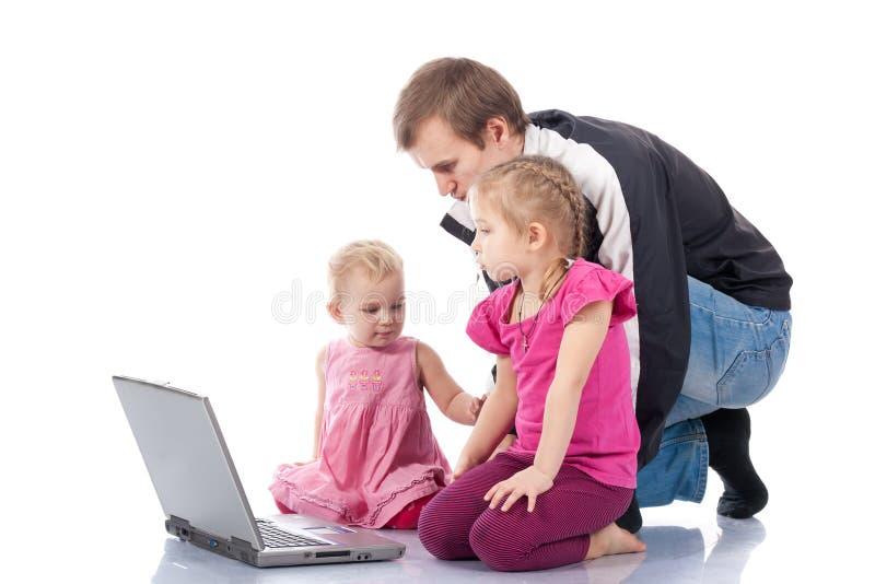 Vater mit den Kindern, die auf Laptop spielen stockbild