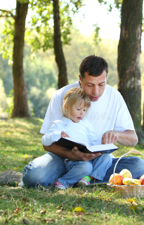 Vater mit einer jungen Tochter las die Bibel in der Natur lizenzfreie stockbilder