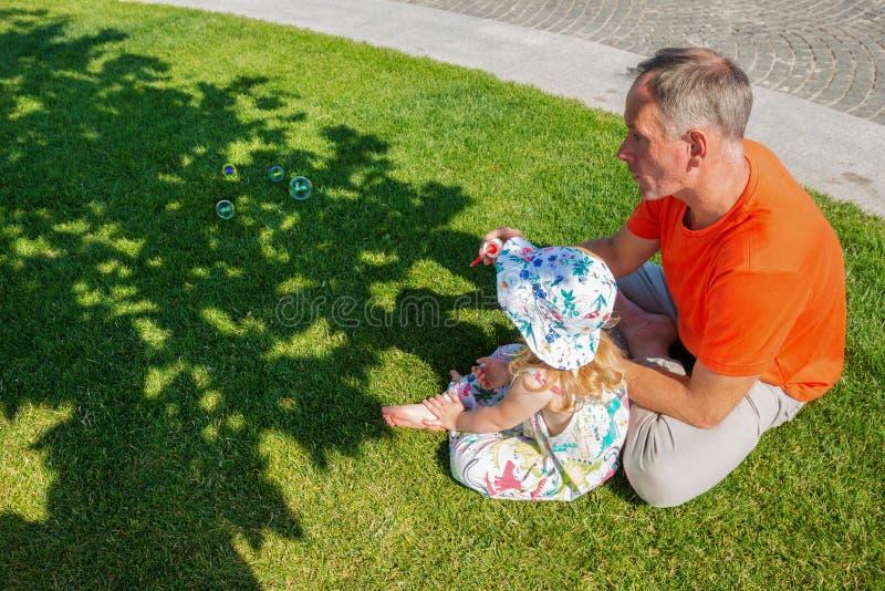 Vater mit einer kleinen Tochter entspannen sich auf einer grünen Wiese stockfotos