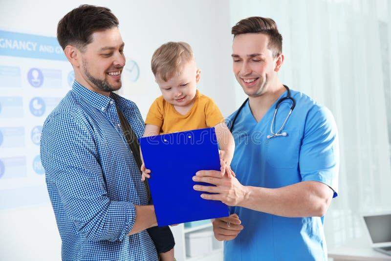 Vater mit Kinderbesuchsdoktor lizenzfreie stockbilder