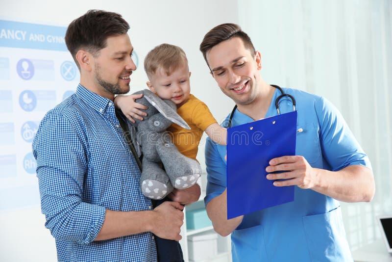 Vater mit Kinderbesuchsdoktor stockfotos