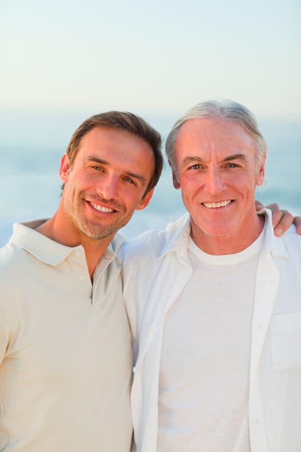 Vater mit seinem Sohn am Strand lizenzfreie stockfotos