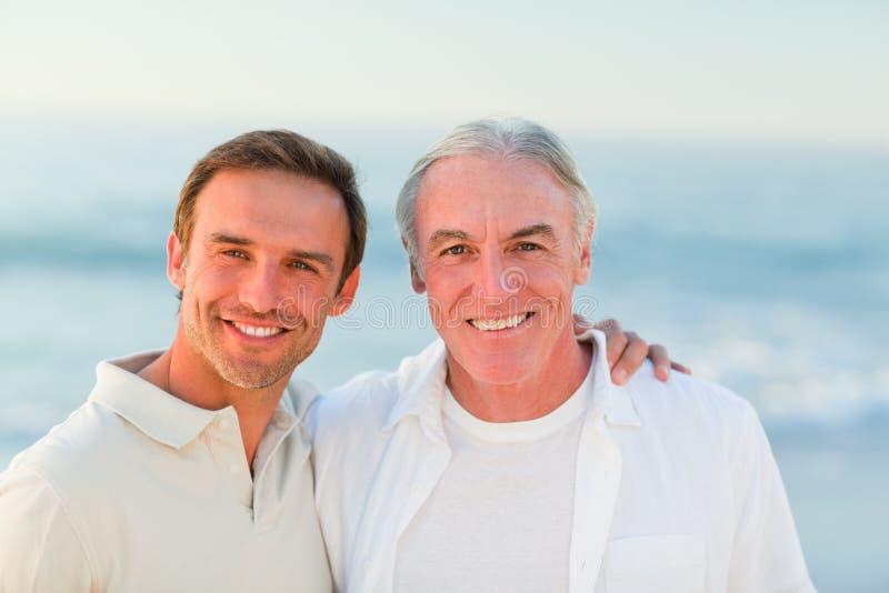 Vater mit seinem Sohn am Strand lizenzfreie stockbilder