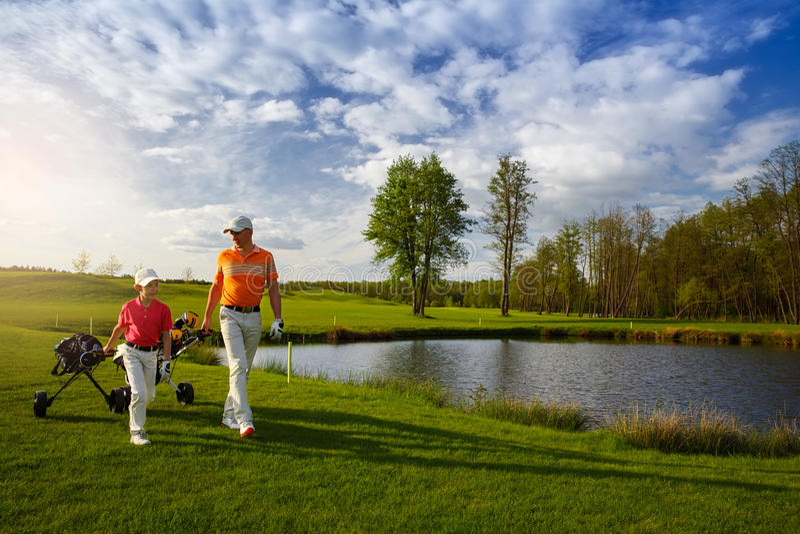 Vater mit Sohn am Golffeld lizenzfreie stockbilder