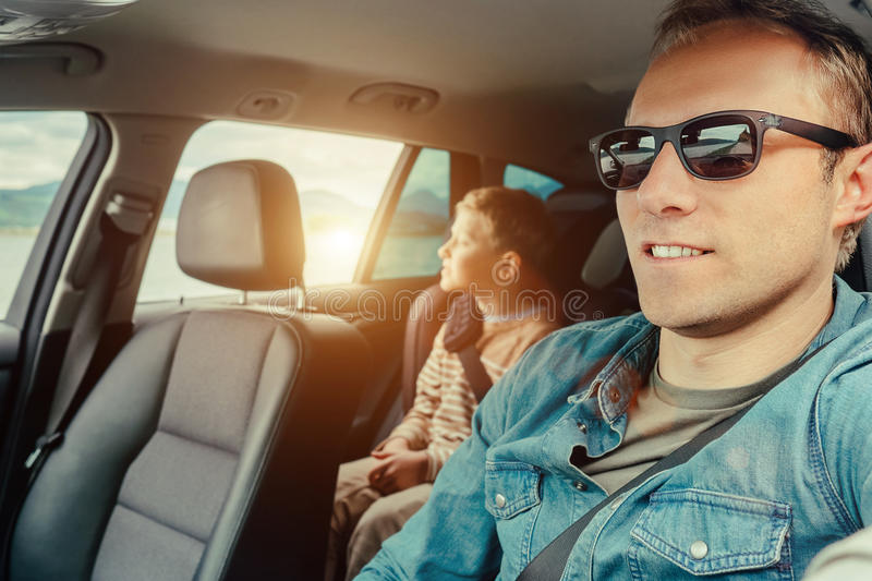 Vater mit Sohn sitzen im Auto lizenzfreie stockfotos