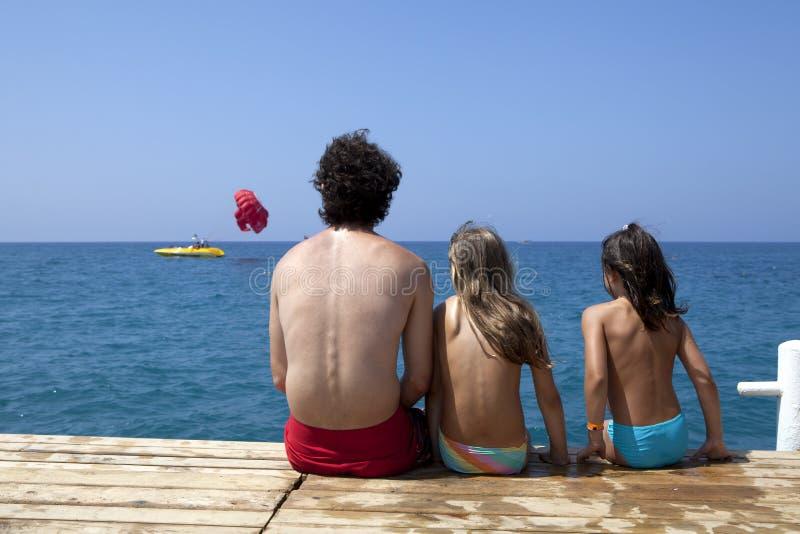 Vater mit Töchtern sitzen auf Piers stockfoto
