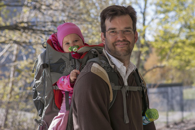Vater mit Tochter im Rucksackträger stockbild