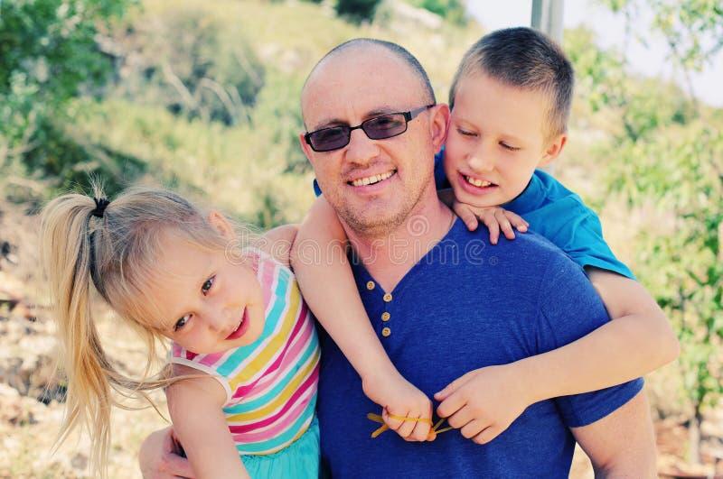 Vater mit zwei Kindern draußen lizenzfreie stockbilder