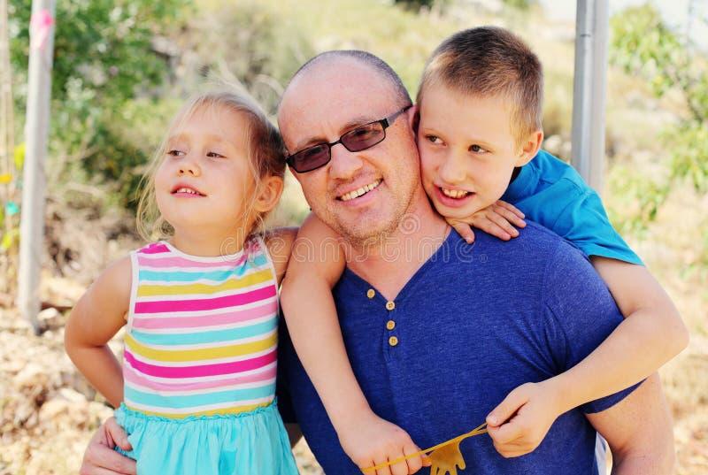 Vater mit zwei Kindern draußen lizenzfreies stockfoto