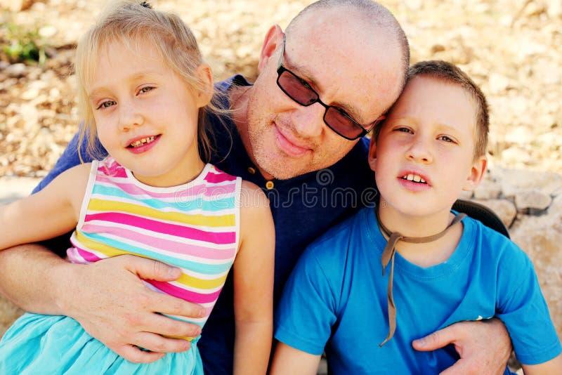Vater mit zwei Kindern draußen stockbild