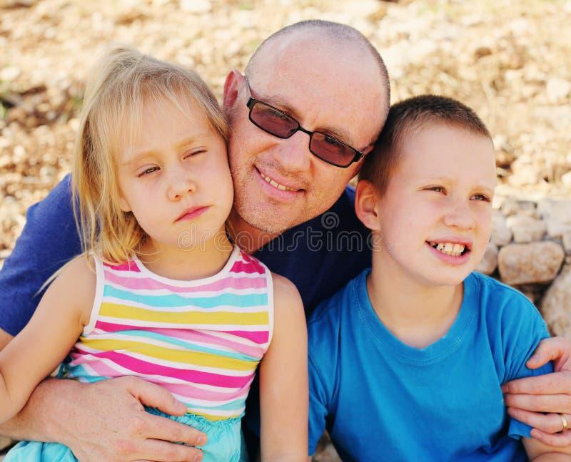 Vater mit zwei Kindern draußen stockfoto