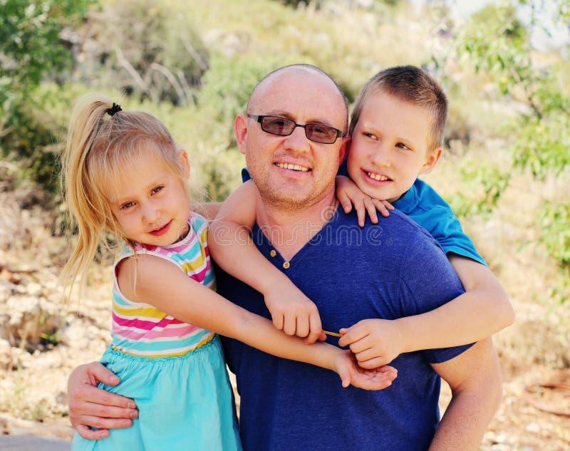 Vater mit zwei Kindern draußen stockfotos