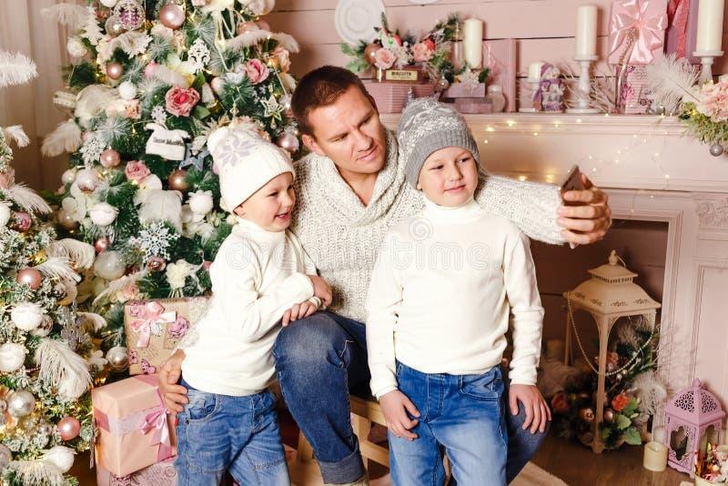 Vater mit zwei Kindern machen Weihnachten-selfi lizenzfreie stockfotos