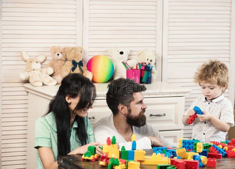 Vater, Mutter und Sohn im Spielzimmer auf hellem hölzernem Hintergrund stockfoto