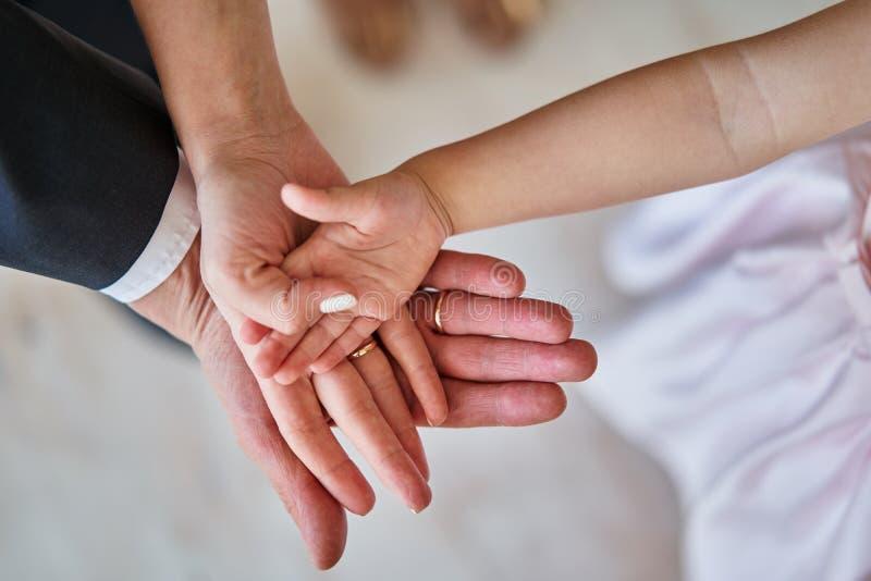 Vater-, Mutter- und Tochtergriffhände zusammen stockfotografie