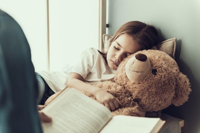 Vater Reading Book zu schlafendem kleinem Mädchen stockbild