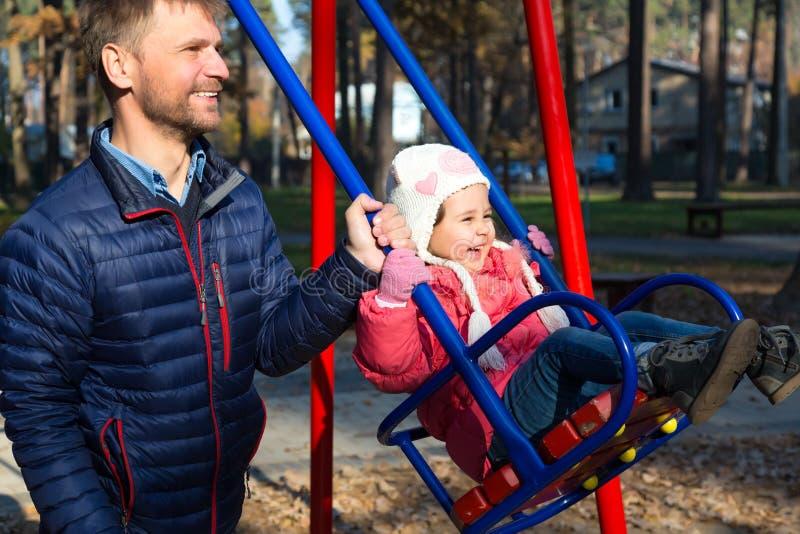 Vater Riding Little Daughter auf ständigem Schwanken im herbstlichen Park lizenzfreie stockfotografie