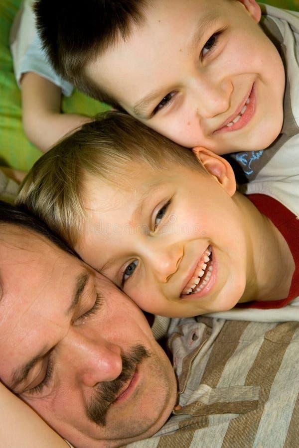 Vater-Schlaf, während Söhne lächeln lizenzfreie stockfotografie