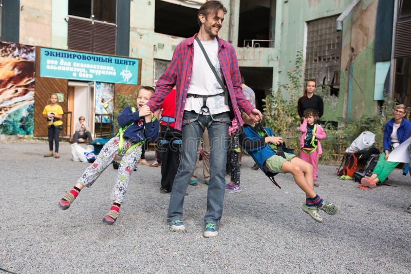 Vater schwingt herum die kleinen Kinder, die an kletterndem Geschirr hängen lizenzfreie stockfotos
