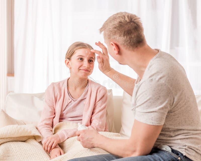 Vater setzt Medizin auf Tochterhautausschlag stockbilder