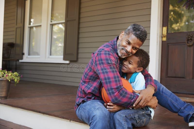 Vater-And Son Discussing-Basketball auf Portal des Hauses lizenzfreie stockfotos