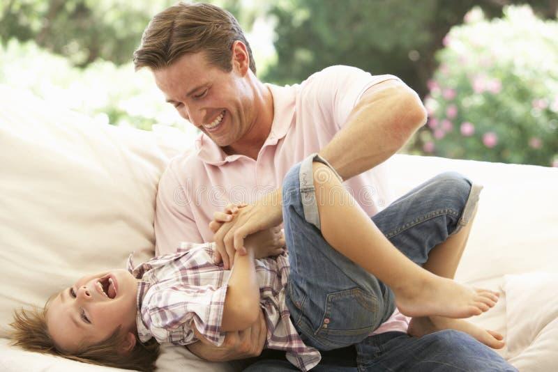 Vater With Son Laughing zusammen auf Sofa lizenzfreies stockfoto