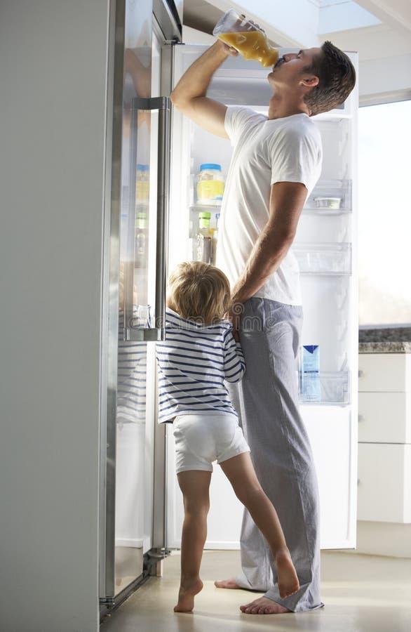 Vater And Son Raiding der Kühlschrank für Getränk stockfotografie