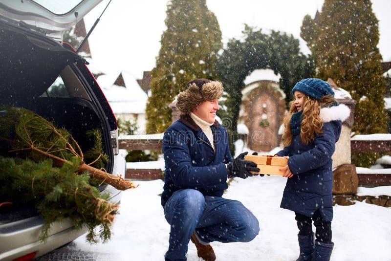 Vater stellt Tochter eine Geschenkbox am Tag des verschneiten Winters draußen dar Weihnachtsbaum im großen Stamm des Familienauto lizenzfreie stockfotos