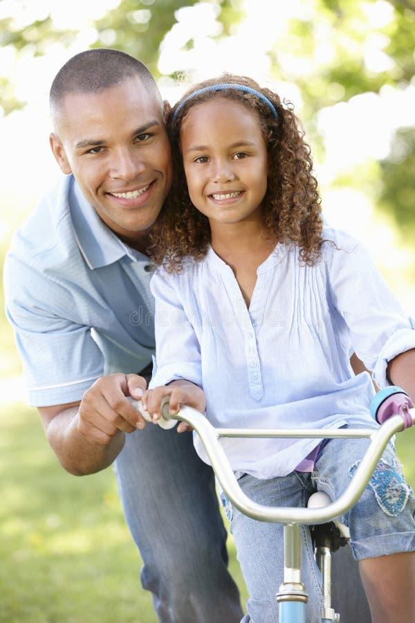 Vater-Teaching Daughter To-Fahrfahrrad im Park lizenzfreie stockfotos