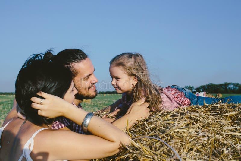 Vater, Tochter und Mutter, die das Leben im Freien auf dem Gebiet genießt lizenzfreie stockfotos