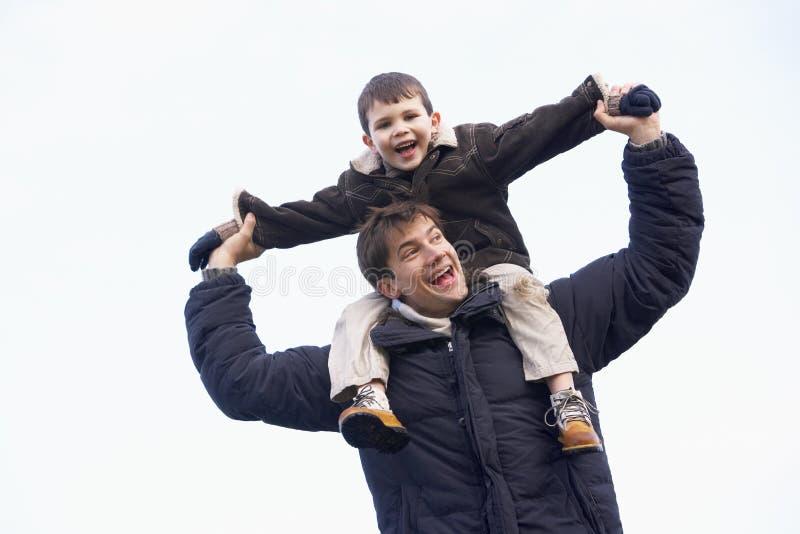 Vater-tragender Sohn auf seinen Schultern lizenzfreie stockfotografie